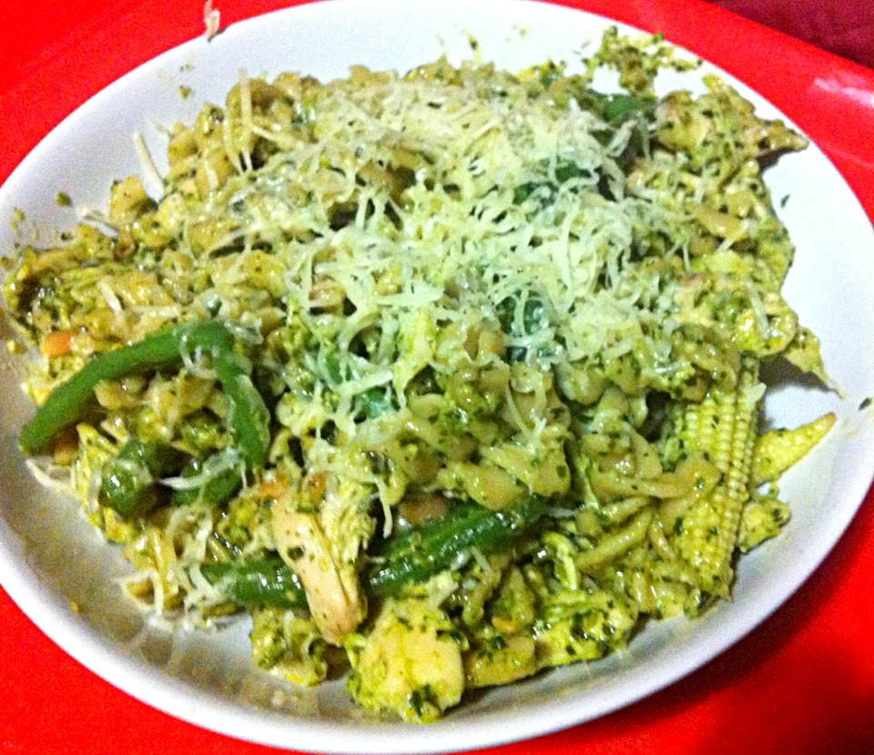 Whole wheat pasta with shredded chicken, toasted pine nuts, babycorn and green beans in a basil and garlic pesto