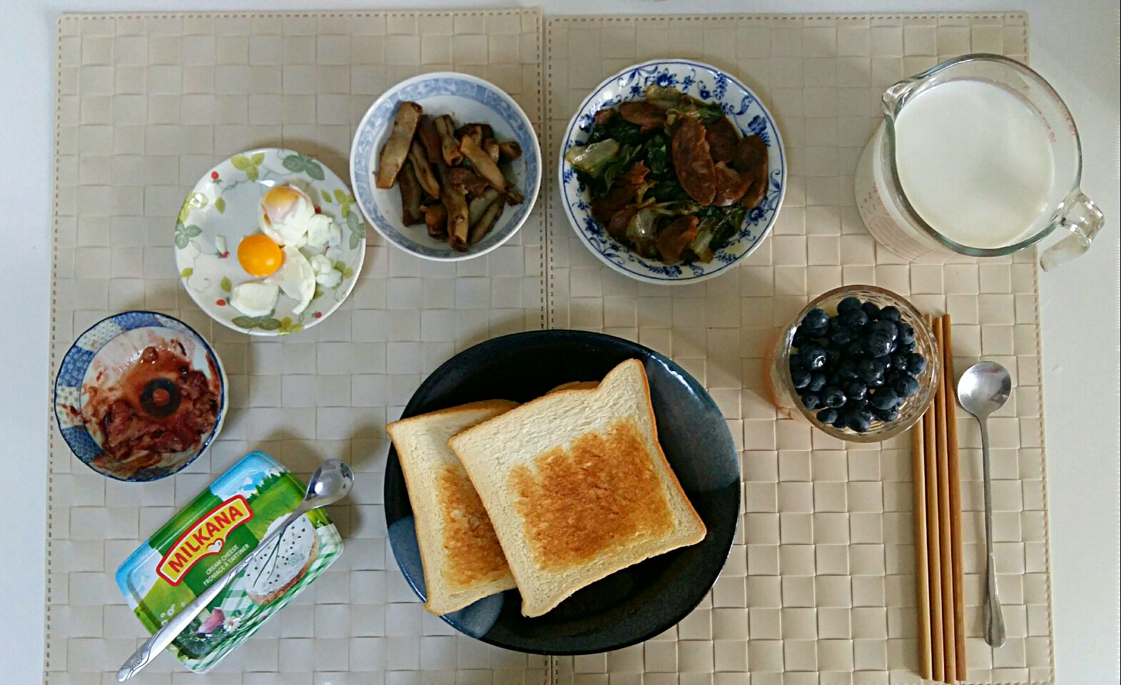 Breakfast for an adult and a kid: furu(tofu made), fried lattuce with sausage, stewed pork with Chinese long beans, boiled eggs, milk, toast, cream cheese.