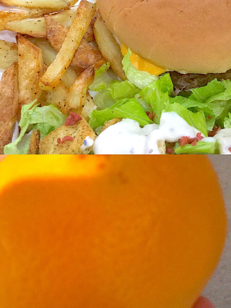 Homemade burgers and fries with a salad and a orange